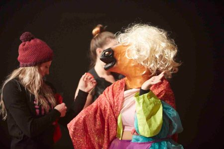 A female audience member wearing a pink beanie is playing dress ups with a dancer who is wearing a blonde wig on top of a horse head mask, a yellow high vis jacket, a pink and orange scarf draped around her shoulders and numerous other items of clothing.