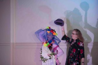 A female audience member wearing glasses and a black dress with red flowers is putting a hat on a dancer who is wearing a blue skirt, wreath of flowers, a white