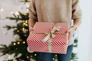 person in gray long sleeve shirt holding red and white striped gift box