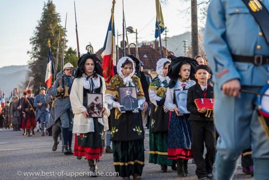 Des enfants en costume alsacien traditionnel portent les photos du capitaine Moufflet et du lieutenant Haas