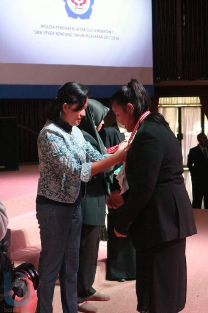 Wakil Ketua DPRD Bontang, Etha Rimba Paembonan mengalungkan medali kepada wisudawan Agama Kristen. (FOTO-FOTO: RERA ANNORISTA/BONTANG POST &  ANSHARI TRI WIBOWO/SMA VIDATRA)