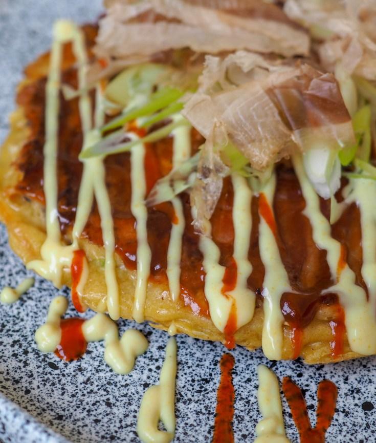 Okonomiyaki er noe av det beste jeg vet. Det er en blanding av en omelett og en pannekake, men det finnes ingen regler for hvordan du lager den. Du tar rett og slett det du har lyst på. Derav navnet som betyr noe slik som «det du vil ha». Denne oppskriften er forholdsvis tradisjonell og det er en oppskrift jeg er veldig glad i. Denne retten blir vanligvis servert på egne puber i Japan, tilberedt på en stekeplate på bardisken rett foran kunden. Denne oppskriften er til en pannekake, som holder til middag for en person.