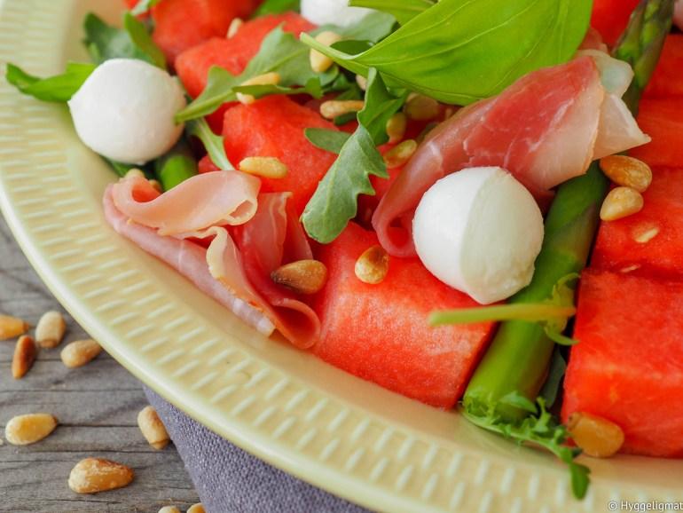 Når det er 30 grader varmt ute og cirka det dobbelte på kjøkkenet er det greit å kunne lage noe som går veldig fort og ikke krever mye arbeid. Det eneste i denne oppskriften som er «plunder» er at du skal dampe asparges og riste noen pinjekjerner. Vannmelon er deilig forfriskende i sommervarmen og sammen med den salte skinken så blir dette et festmåltid. Denne porsjonen holder som en liten lunch til fire stk eller middag for to.
