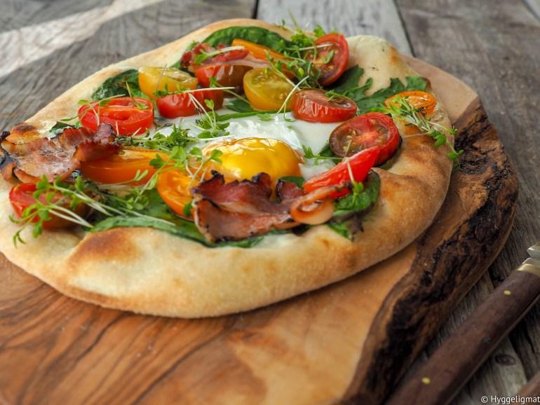 Pizza er noe av det beste som finnes. Det at du kan ha absolutt hva som helst på en pizza, gjør at du kan spise en ny pizza hver dag resten av ditt liv, uten å spise den samme to ganger. Pizza i prinsippet bare en brøddeig med topping, altså en en brødskive med pålegg. Så da vil jeg gjerne slå et slag for pizza til frokost. Her er en variant med egg, bacon, saftige tomater og litt spinat.