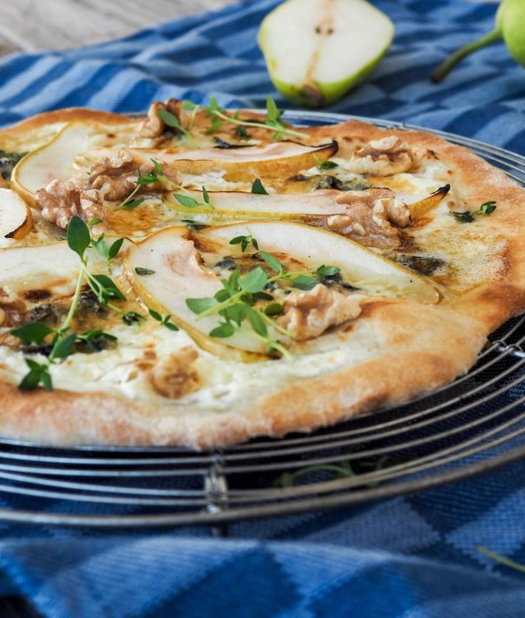 Pizza er skikkelig morsom mat som man kan leke med i det uendelige. Topping kan varieres herfra til månen. Fugl, fisk, kjøtt, rogn, grønnsaker, frukt.. Bare fantasien setter grenser for hva du kan ha på pizzaen din. Her har jeg ikke vært spesielt fantasifull, men det det er uansett mange spennende smaker bakt sammen til en nydelig pizza. Salt fra blåmuggosten, pærene står for friskhet og syrlighet, valnøtter for litt bitterhet og tilslutt litt sødme fra honningen. Dette er nesten som et ostefat hvor du også kan spise fatet.