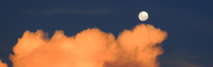 Bright moon in dusk sky with sunset-red clouds in foreground