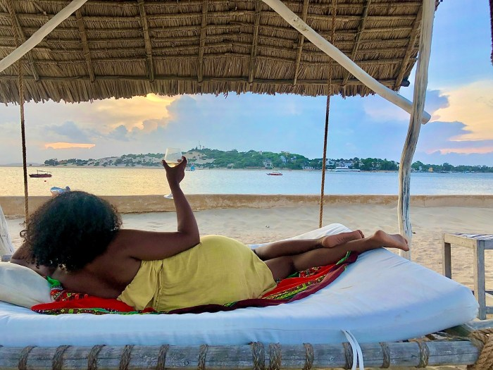 Black woman lounging on beach in Mozambique