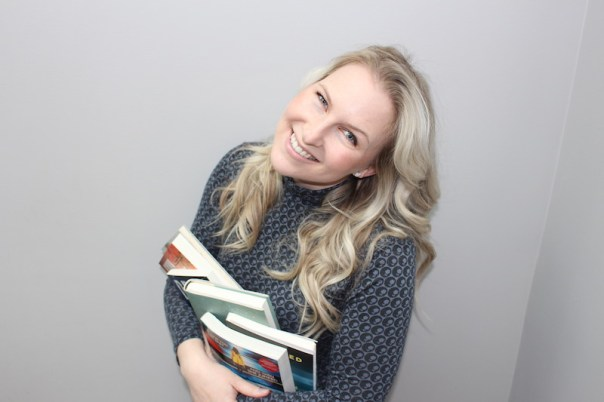 Portrait of book blogger Anne Logan, holding a stack of books
