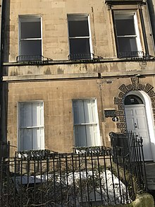 Front view of a house in Bath occupied by Jane Austen . Shows steps leading to an arched door.