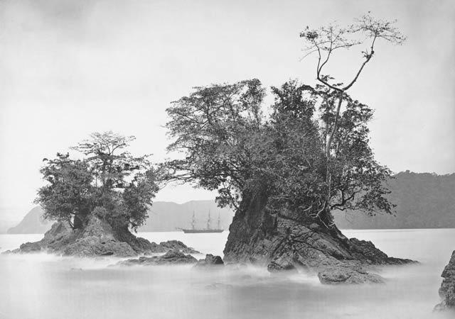 View of Three-Masted Sailing Ship Between Tree-Covered Rock Formations in Misty Harbor, 1870