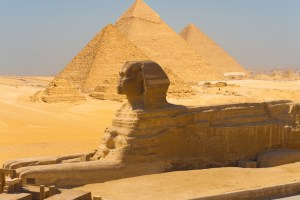 A side view of the great Sphinx with all of the pyramids of Giza in the background in Cairo, Egypt
