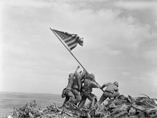 The Raising of the Flag on Iwo Jima, where 5 US Soldiers lift an American flag in team effort.