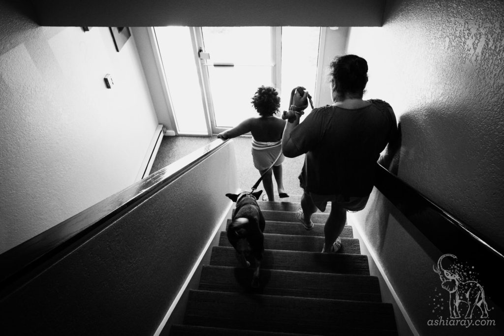 Mother and daughter exit apartment with their therapy dog