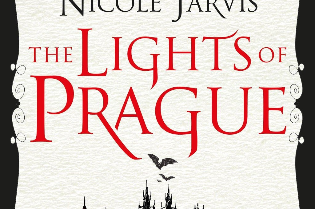 Cover for 'The lights of prague' by Nicola Jarvis. The background is white with the author's name appearing first in black letters followed by the title underneath in red. The bottom of the cover features an overview of historical prague, while there are bats in the top left corner above the author's name.