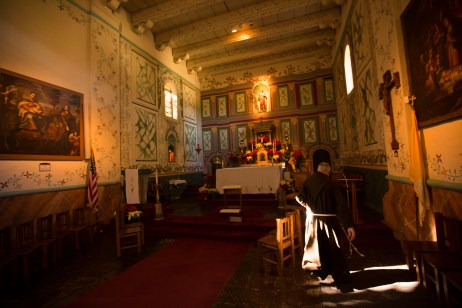 A Franciscan Padre makes his way behind the main altar at Mission Santa Inés. (Original traditions.)