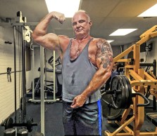 Me at 60 in my basement gym, with my Powertec behind me.