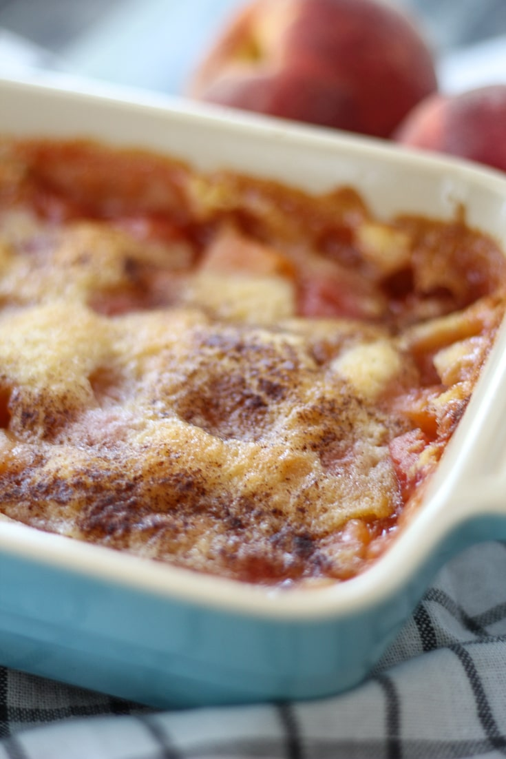 Easy Peach Cobbler in a pan with two fresh peaches in the background.