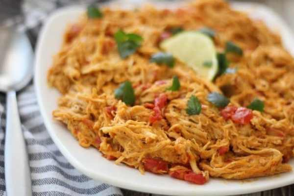 shredded Mexican chicken on a plate with cilantro and lime wedge