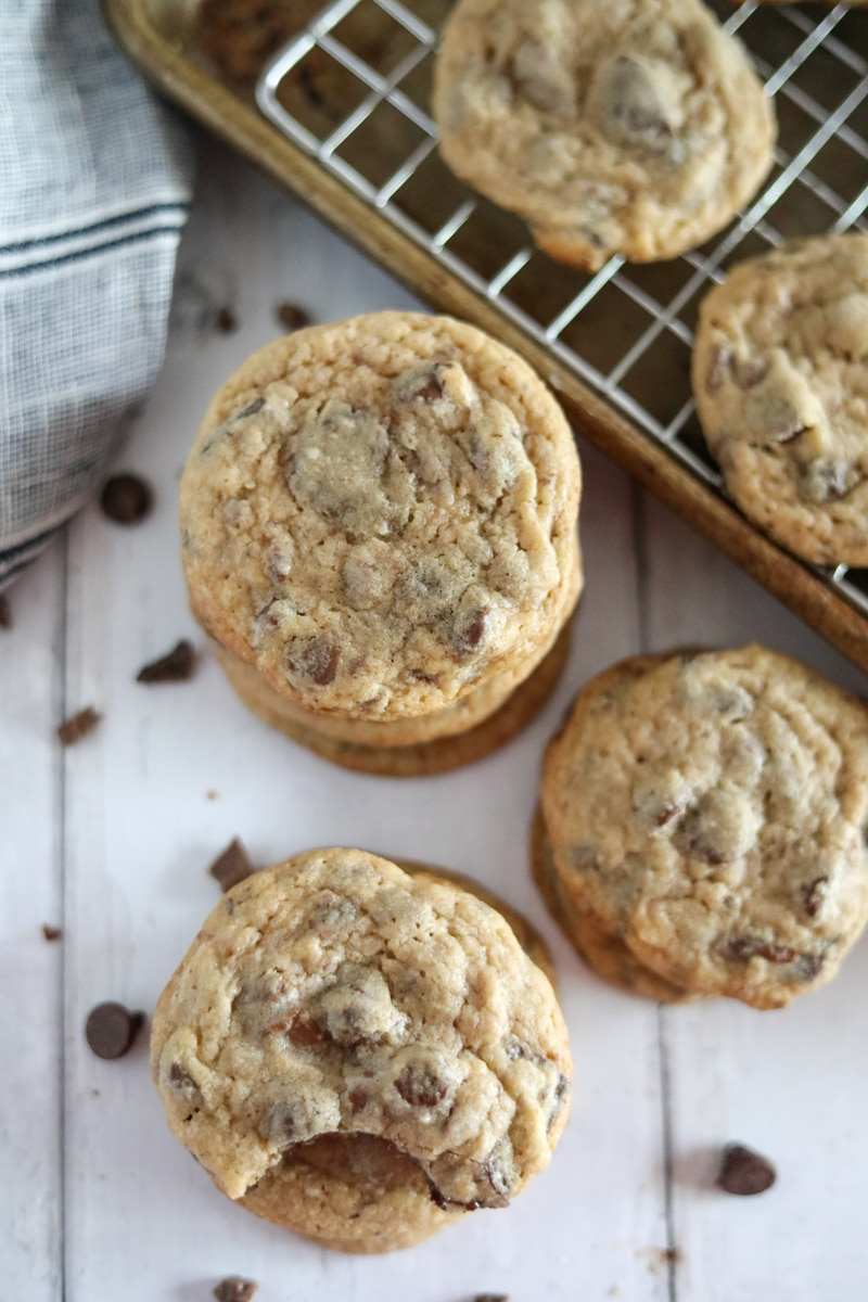 three stacks of chocolate chip cookies with a sheet pan in the background