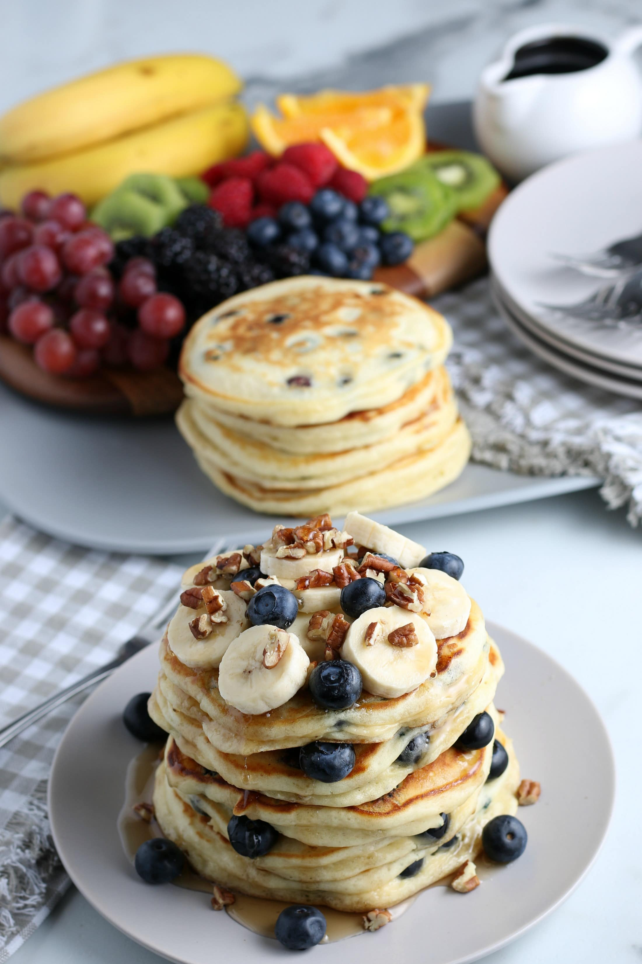 A stack of blueberry pancakes with fruit n the background.