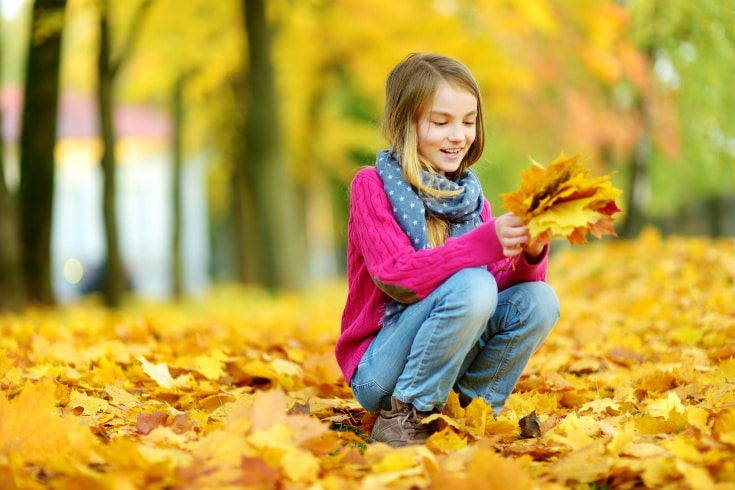 girl collecting leaves for autumn bucket list