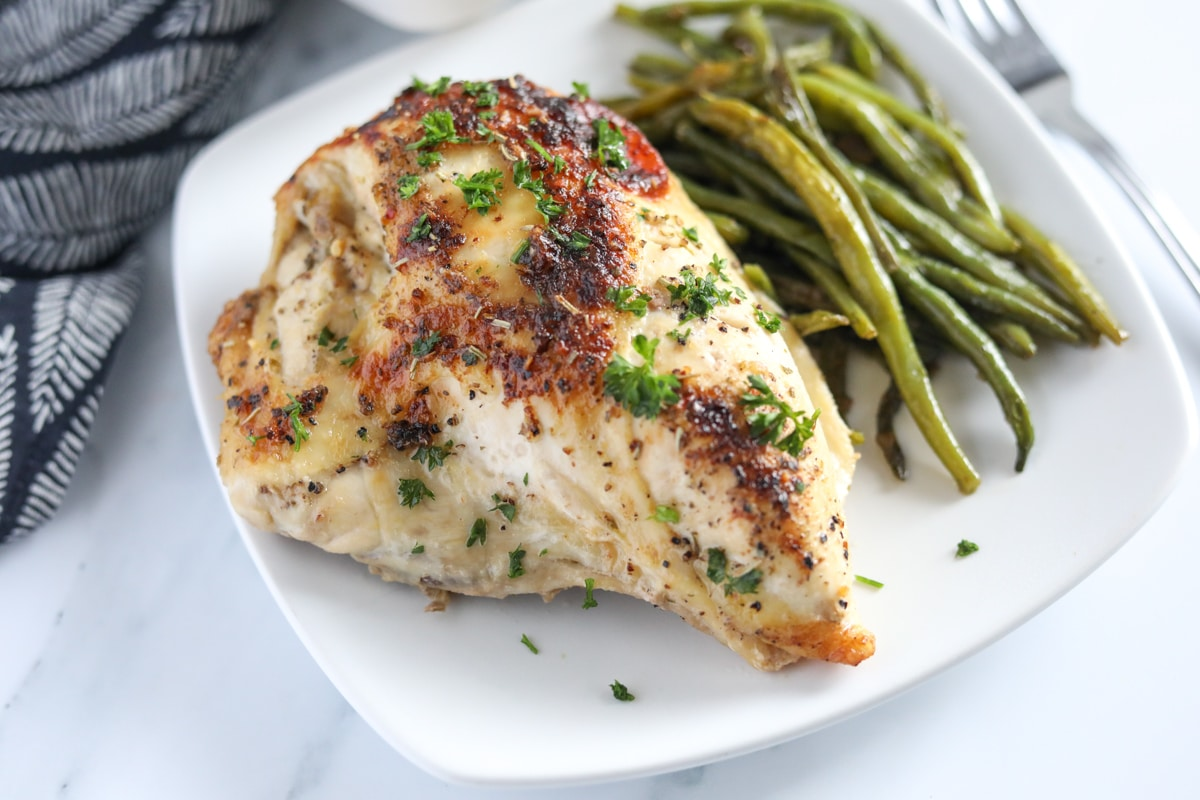 Baked italian chicken breast on a white plate with green beans on the side.
