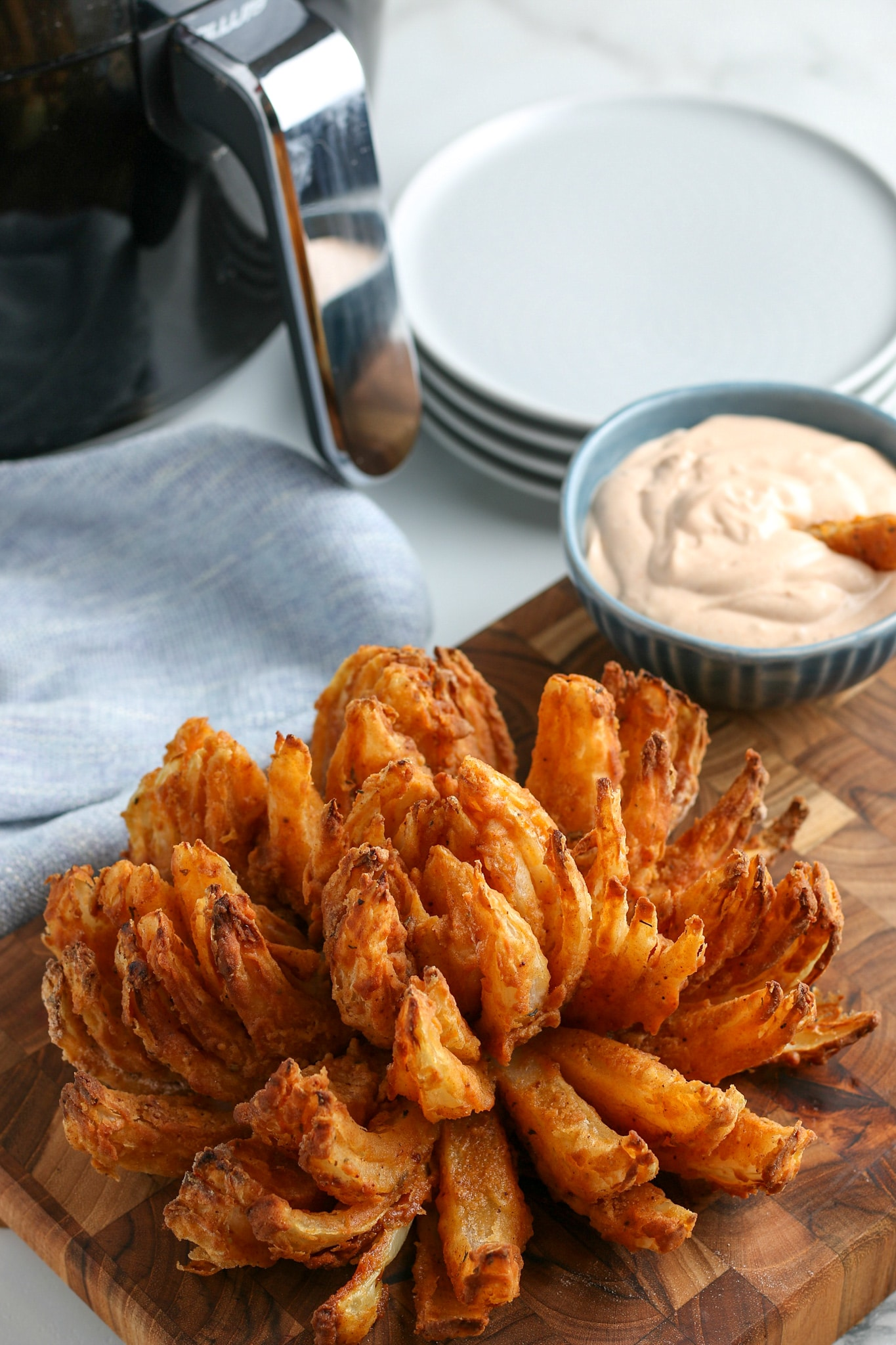 the finished air fried blooming onion recipe with horseradish sauce in the background.