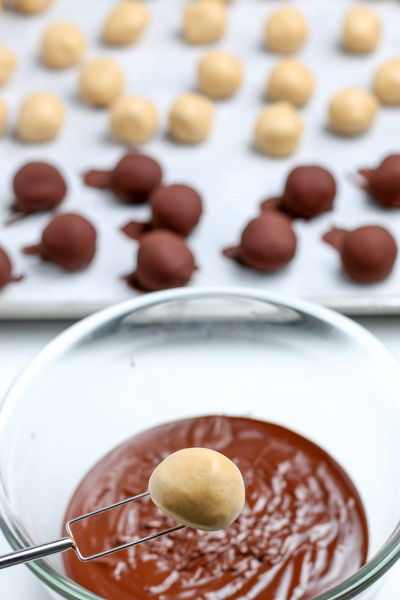 peanut butter balls ready to be dipped in the melted chocolate with a chocolate dipping fork.