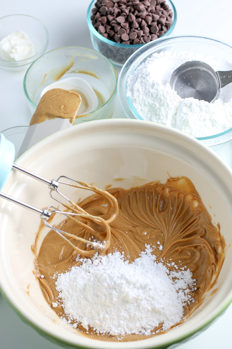 peanut butter and butter mixture with powdered sugar in a white mixing bowl.