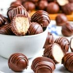 Peanut butter balls stacked in a white glass bowl