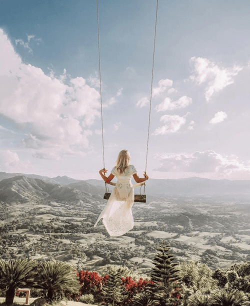 A woman flies high in a swing - @the_essentialist_