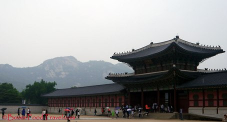 Mountains surrounding Gyeongbokgung with people flowing into the palace in the rain