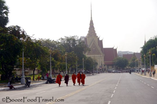 Monks walking along the street in front of the palace in Phnom Penh