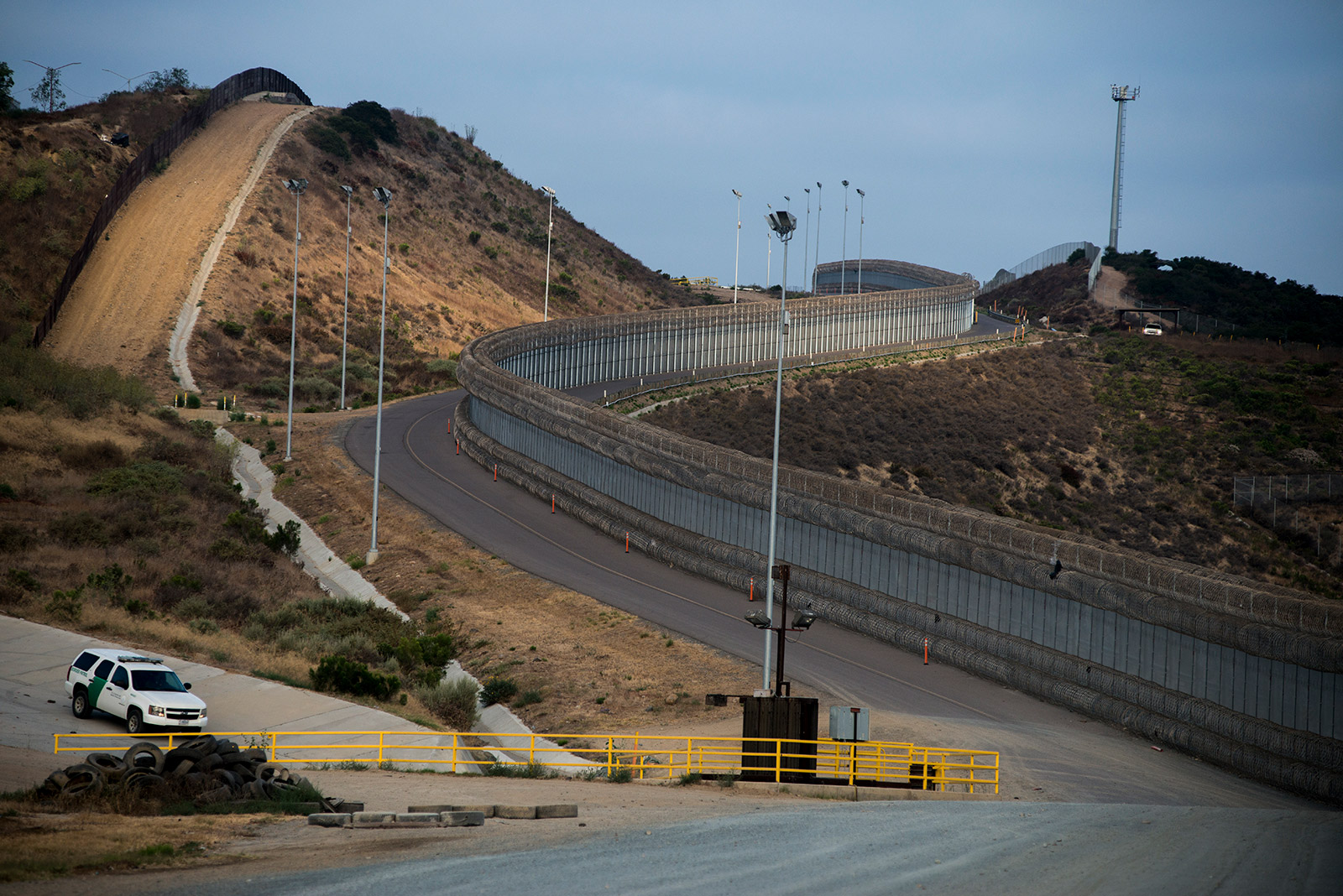 """A section of secondary fencing, covered with concertina wire at the base and top of the structure, snakes along a winding road near the San Ysidro Port of Entry in San Diego on Aug. 16, 2017. Also shown is a line of primary fencing made of corrugated steel, left, a Border Patrol vehicle along a drainage area and a tower with """"virtual fencing"""" technology at the top of the hill. <em>(Brandon Quester/inewsource)</em>"""