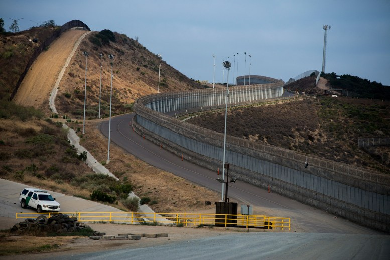 "A section of secondary fencing, covered with concertina wire at the base and top of the structure, snakes along a winding road near the San Ysidro Port of Entry in San Diego on Aug. 16, 2017. Also shown is a line of primary fencing made of corrugated steel, left, a Border Patrol vehicle along a drainage area and a tower with ""virtual fencing"" technology at the top of the hill. <em>(Brandon Quester/inewsource)</em>"