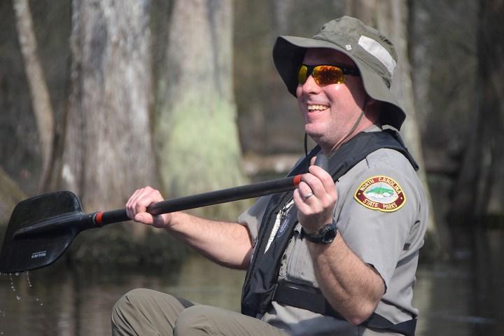 Lane Garner, superintendent at Lumber River State Park is paddling a canoe.