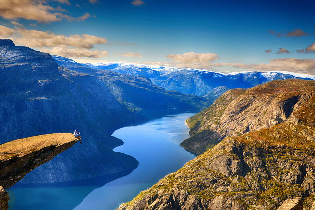 Read newspaper on the top of Trolltunga by Alexander Artworkx