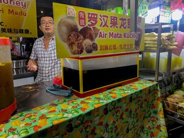 Man serving Air Mata Kucing in Jalan Alor Night Market in Kuala Lumpur Cheap Eats Food Tour