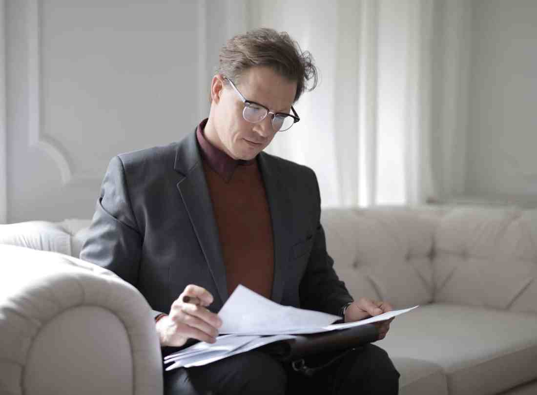 classy executive male reading papers on couch