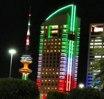 Buildings in Kuwait light up in Kuwait colors.