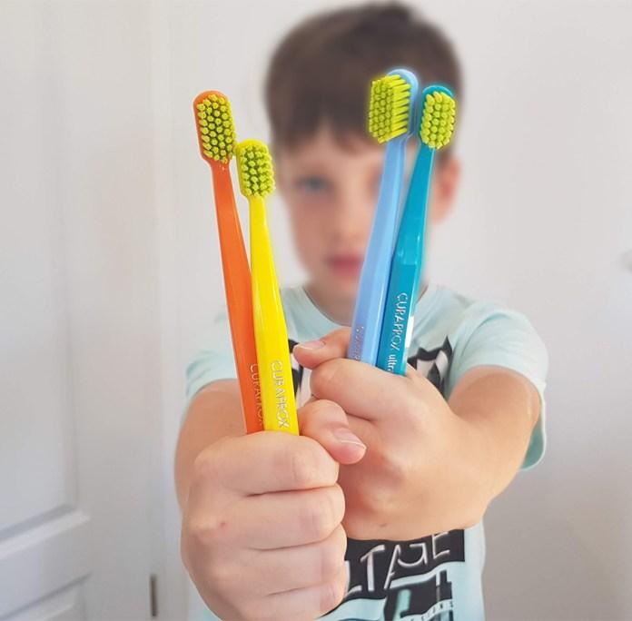 dreng med curaprox tandbørster i hånden
