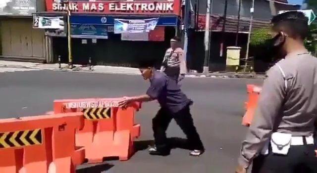 NGAMUK: Seorang pria di Wonosobo memindahpaksakan barikade jalan . (Sumber: tangkapan layar video)