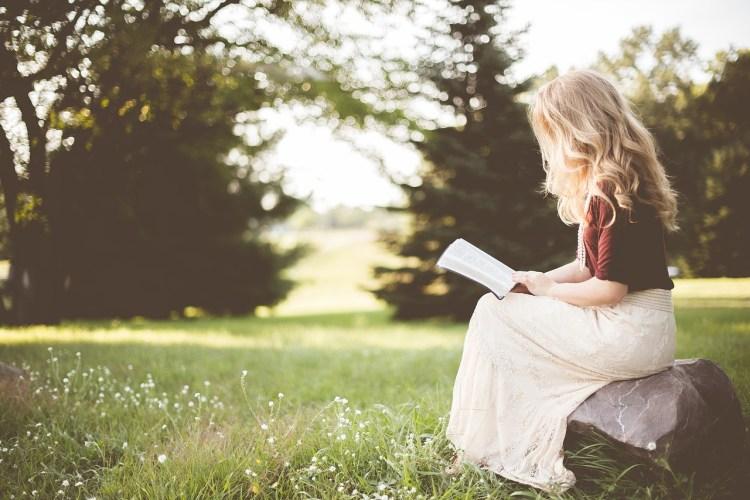 Kobieta czyta siedząc w ogrodzie