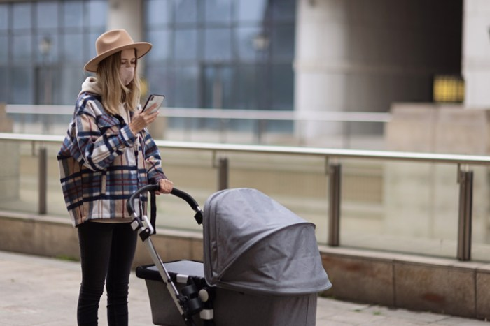 Happy Mother Walking With Stroller In Park And Using Mobile Phone. Joy Of Motherhood. Stylish Woman