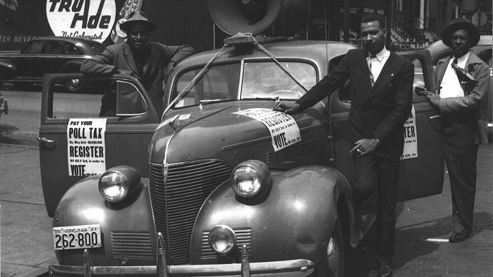 Three men standing around a car with signs for the Crusade for Voters
