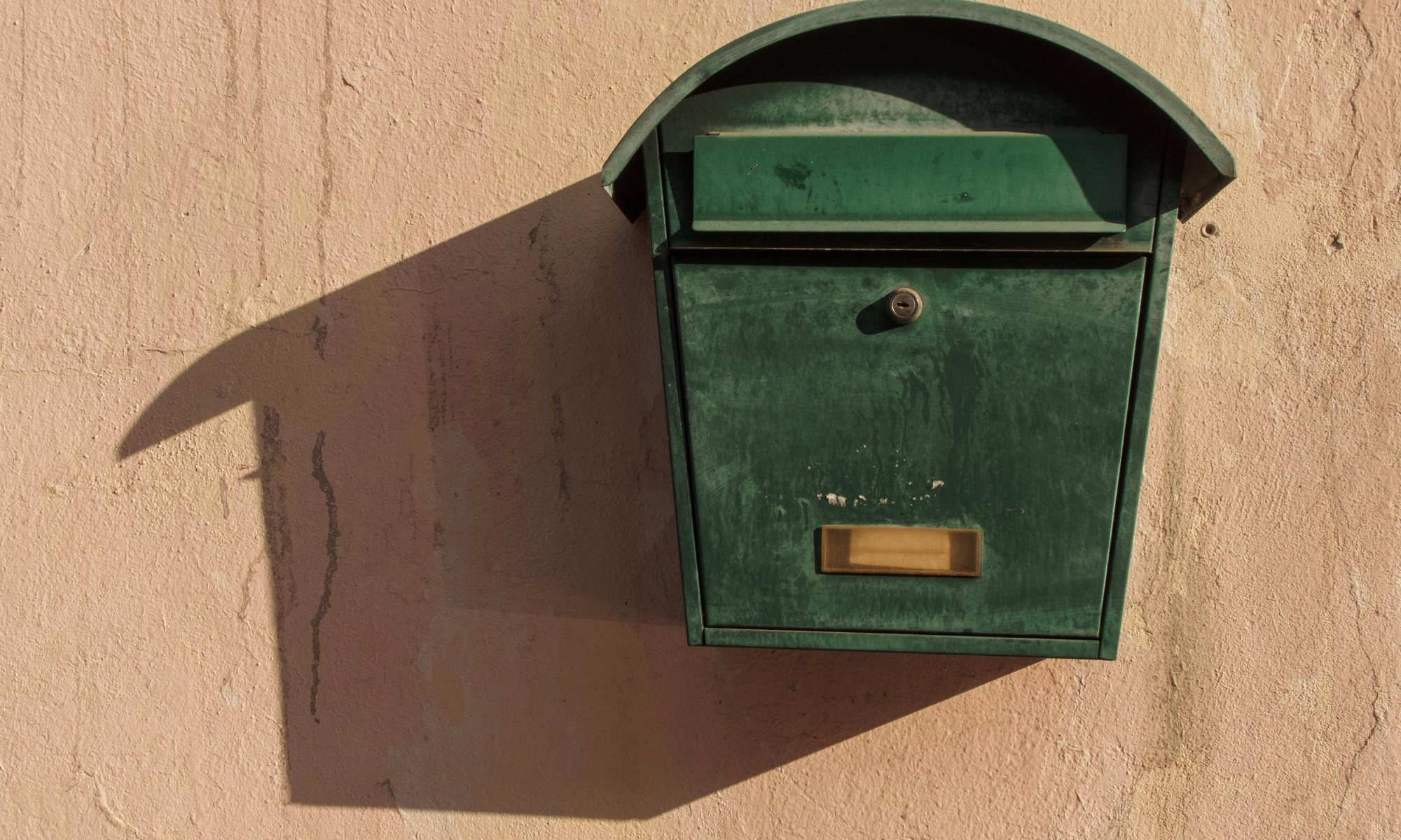 Green mailbox. The old green mailbox on the wall with big shadow.