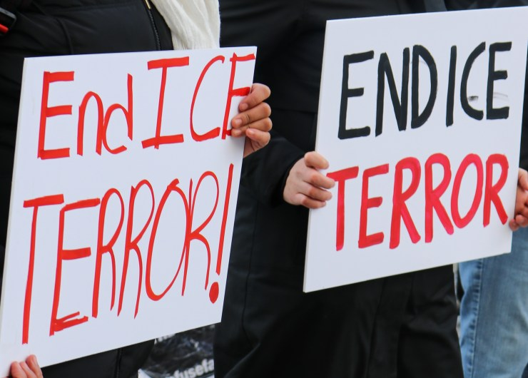 """Photo with two signs in black and red reading """"End ICE Terror"""""""