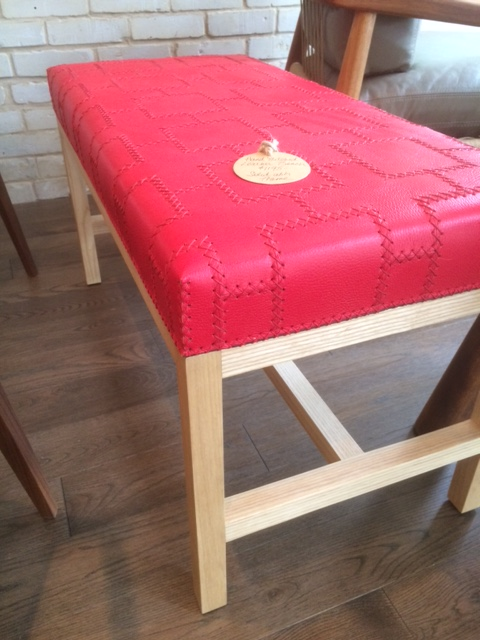 """They've got you covered there too! Hand-stitched 34"""" leather bench in red $1,195"""