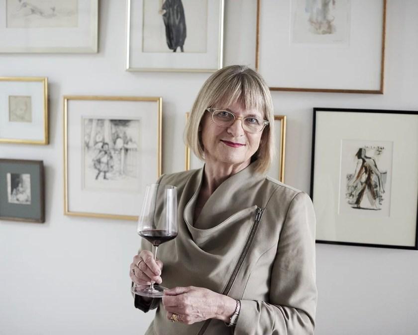 Weinkritikerin Jancis Robinson zuhause im Flur vor Wandbildern mit einem Glas Wein in der rechten Hand