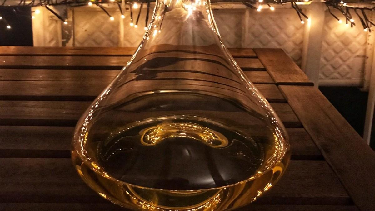 Weißwein in einem Dekanter, auf einem Balkon am späten Abend, an dem es schon dunkel ist - im Hintergrund brennt eine Lichterkette